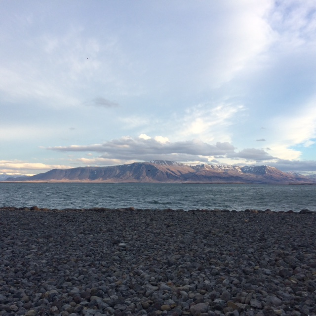 view of volcanoes from the shore in the morning